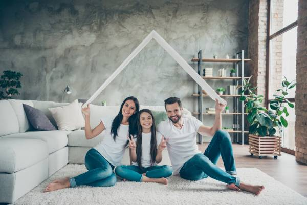 Portrait of nice attractive cheerful family in casual white t-shirts jeans sitting on carpet floor holding in hand roof real estate ownership showing v-sign at industrial loft style
